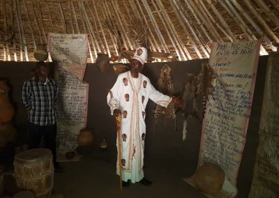 Rwot Damoi show casing cultural regalia to Amani Insitute during reparation.
